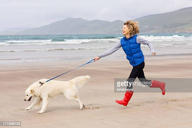 Woman Running With Dog On Beach