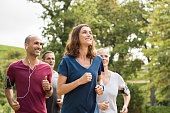 Mature woman running with group of people at park. Happy smiling woman with group of friends running together. Senior runners team on morning training.
