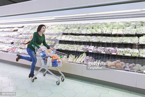 Woman running with shopping cart in supermarket produce aisle