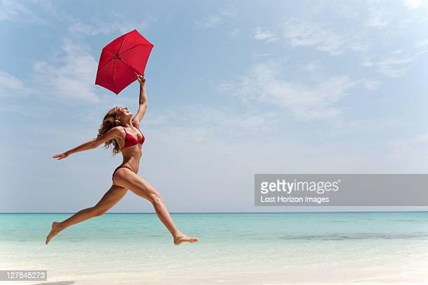 Woman running with umbrella on beach