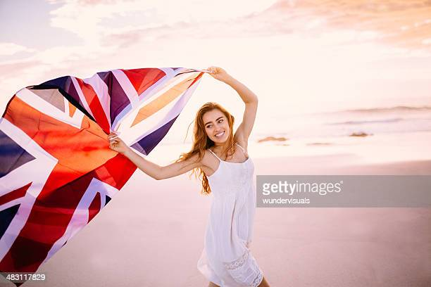 Woman running with Union Jack on beach
