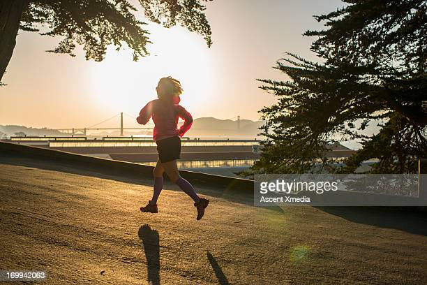 Woman runs along waterfront, sunrise