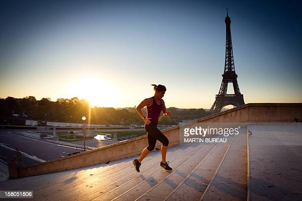 A woman runs as the sun rises on the Eiffel tower on September 21 2010 in Paris AFP PHOTO / MARTIN BUREAU