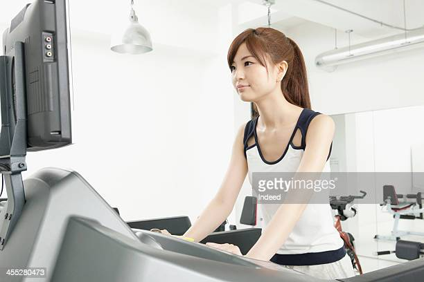 Woman runs by treadmill