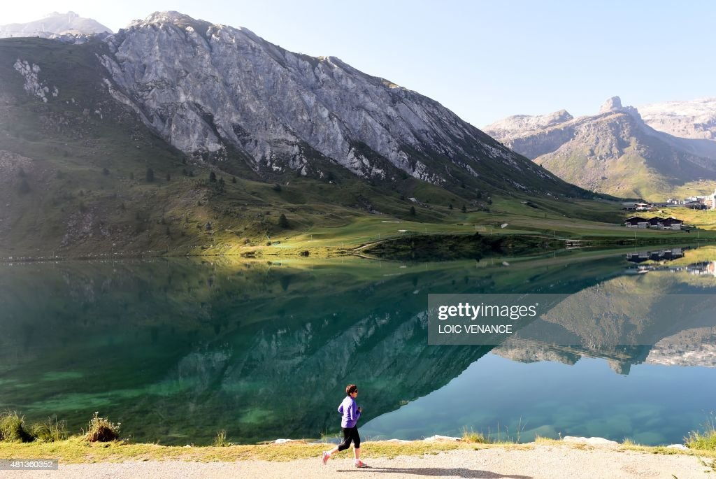A woman runs in front of the TignesValClaret ski resort on July 20 2015 in Tignes AFP PHOTO / LOIC VENANCE