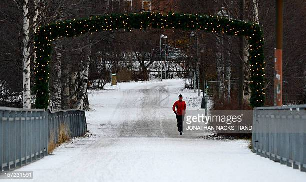 A woman runs in the city of Ostersund Sweden on November 30 2012 Meteorologists forecast temperatures around minus 10 degrees in southern Sweden for...