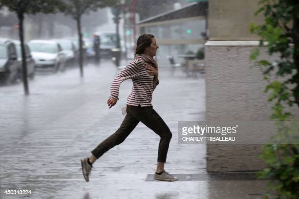 A woman runs in the street under the rain on June 9 in Caen northwestern France 41 regions of France were under alert this evening as many storms...