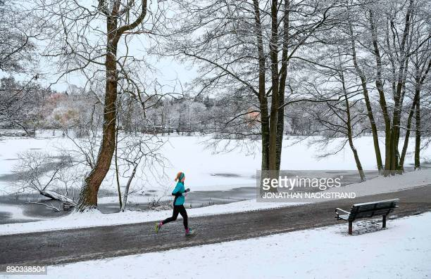 A woman runs next to Lötsjön lake after snow fall on December 11 2017 in Sundbyberg near Stockholm High winds and heavy snow in Europe on Monday...