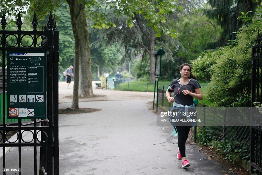 A woman runs on May 29, 2016 at the entrance of the Parc Monceau the day after eleven people including ten children were struck by lightning in the park in Paris.