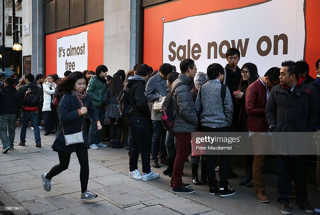 A woman runs past a line of shoppers waiting to enter Selfridges department store on December 26, 2012 in London, England. Thousands of shoppers are in London looking for a bargain in the traditional Boxing Day sales.