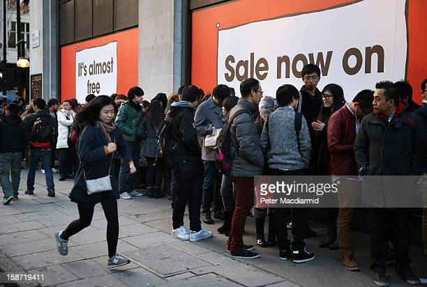 A woman runs past a line of shoppers waiting to enter Selfridges department store on December 26 2012 in London England Thousands of shoppers are in...