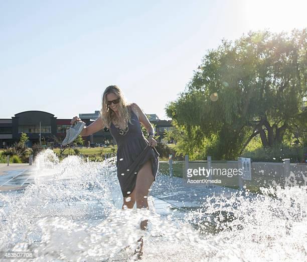 Frau läuft über den Gehweg-Brunnen in city