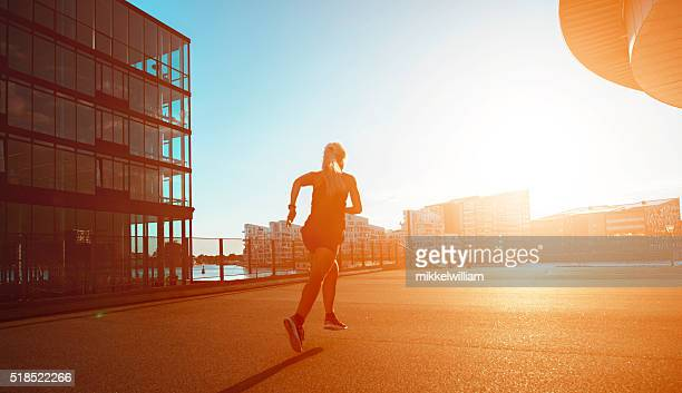 Woman runs towards sunset in the city