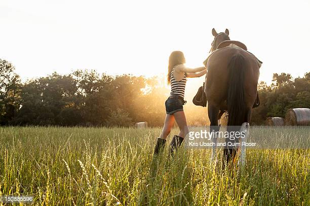 Woman saddling up horse in field