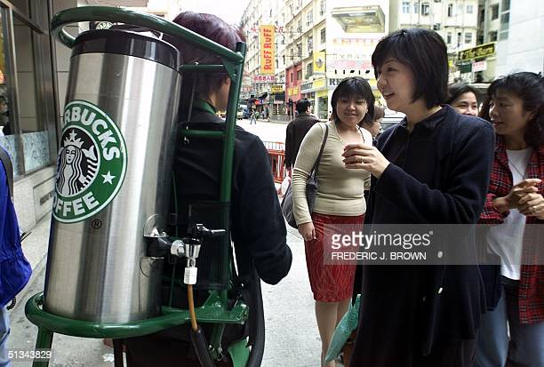 A woman samples a cup of coffee from 'Mercury Man' a Starbucks employee who walks around with a pot of coffee on his back 29 November 2000 in Hong...