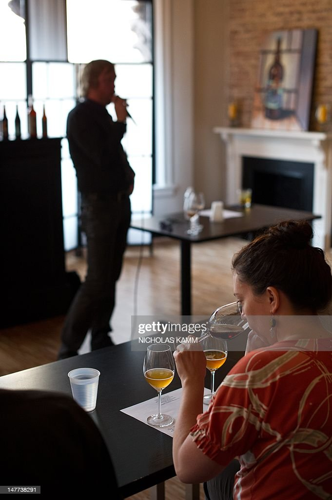 A woman samples beer as she listens to Greg Engert, head brew guru at ChurchKey/Birch & Barley, during a beer history event at Living Social in Washington on June 26, 2012. Online coupons are last year's news.That is the view from number two US online deals firm Living Social, which is battling sector leader Groupon by offering what excutives call 'unique' or original experiences that are not simply linked to discounts. AFP PHOTO/Nicholas KAMM