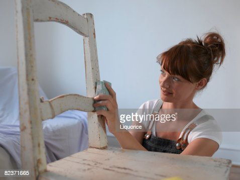 woman sanding chair : Stock Photo