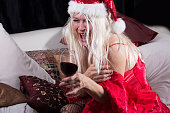 Woman Santa Clause alone and sad at Christmas with wine