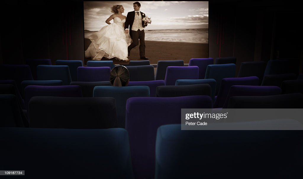 Woman sat alone in cinema watching romantic film : Stock Photo