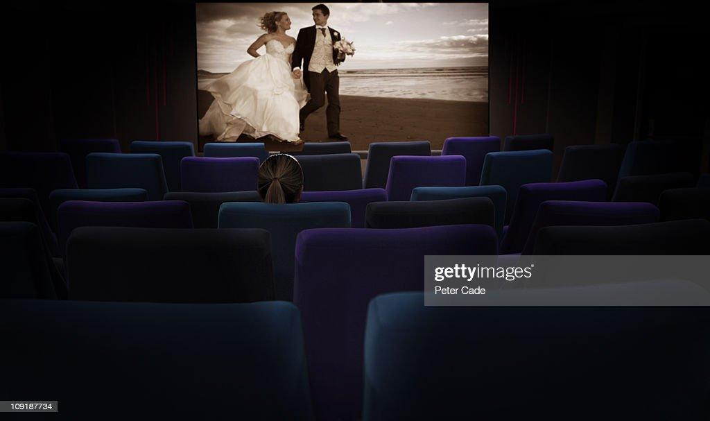 Woman sat alone in cinema watching romantic film