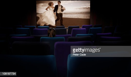Woman sat alone in cinema watching romantic film