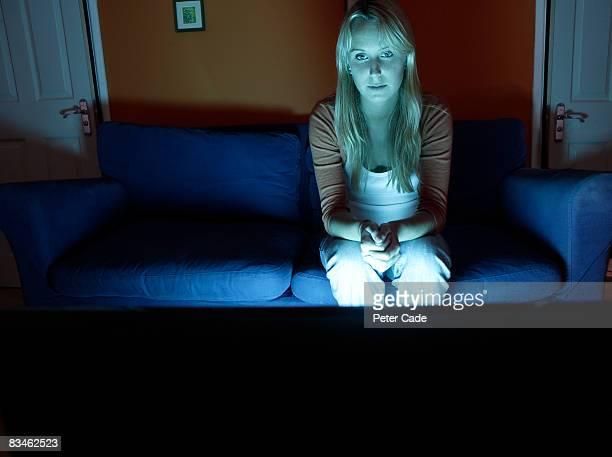watching tv at night. woman sat alone watching television tv at night