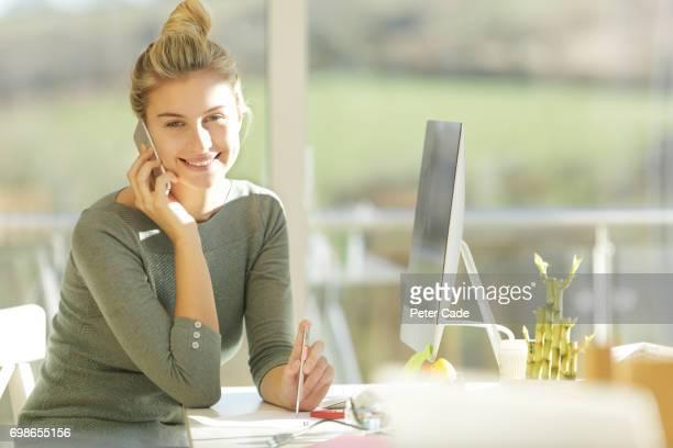 Woman sat in modern office talking on phone