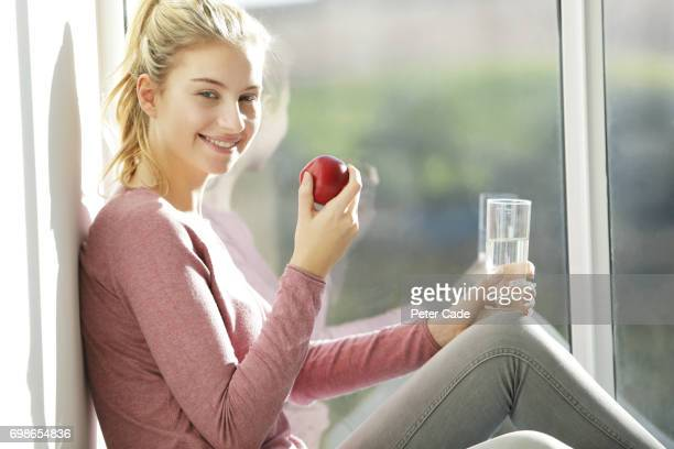 Woman sat in window with glass of water and apple