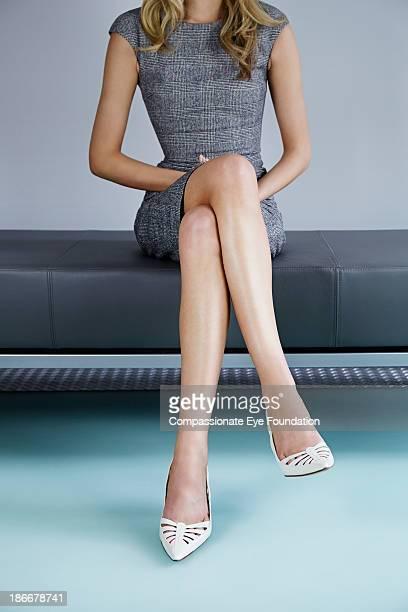 Woman sat on bench, legs crossed