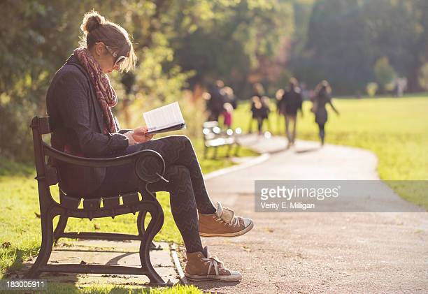 Woman sat on bench reading a book