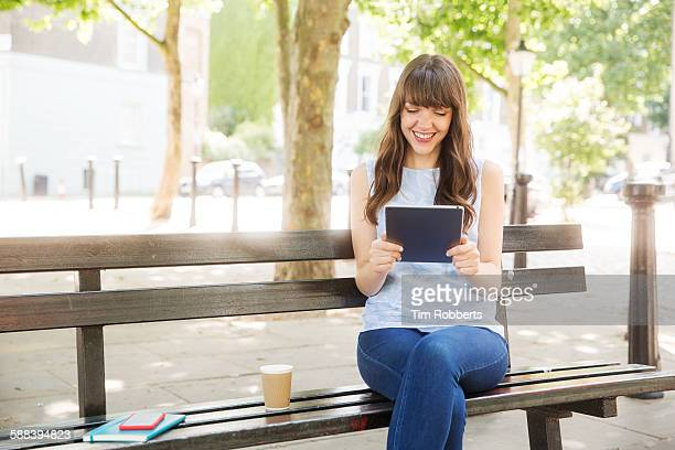 Woman sat on bench with tablet.