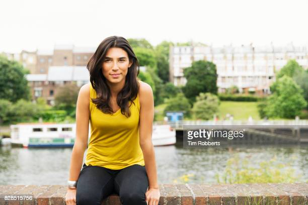 Woman sat on wall looking at camera