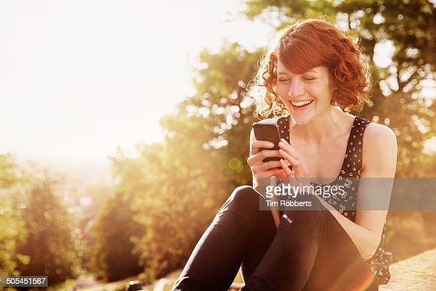 Woman sat on wall using smartphone.