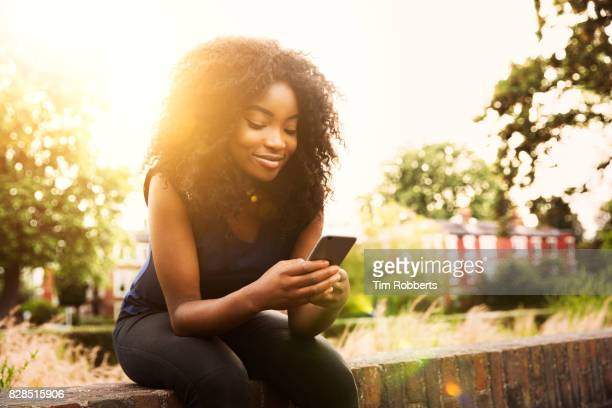 Woman sat on wall with smart phone at sunset