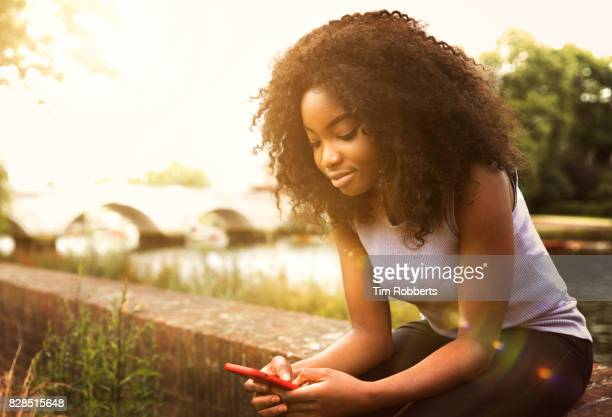 Woman sat on wall with smart phone
