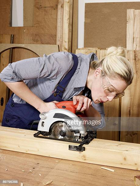 A woman sawing wood