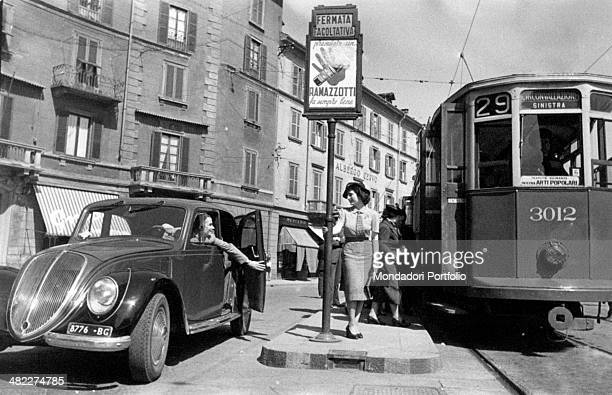 A woman saying hallo to another woman on board a car before getting on the tram Milan 1950s
