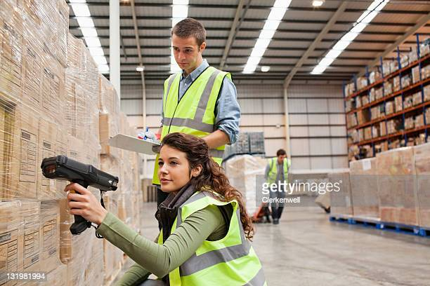 Woman scanning barcodes while young man with checklist