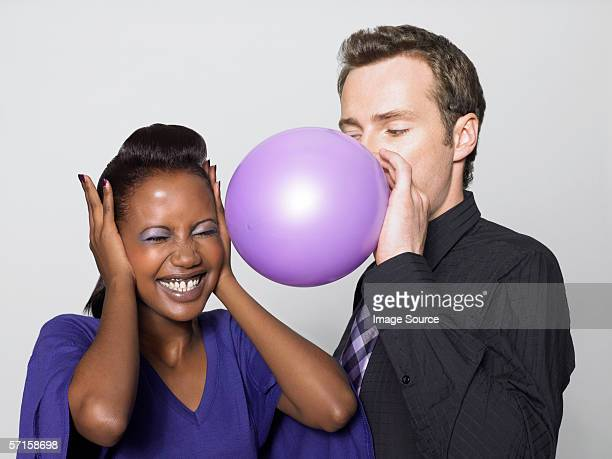 Woman scared of man blowing balloon