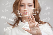 Woman scientist or student working with various high school maths and science formula standing on gray background.