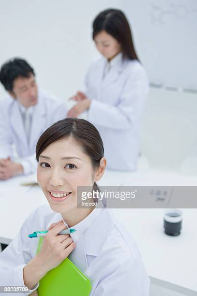 Woman scientist smiling by table, people in behind