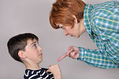 Woman scolding and pointing her index finger at the scared young boy