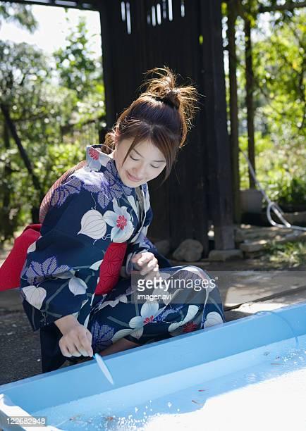 Woman scooping goldfish with kimono