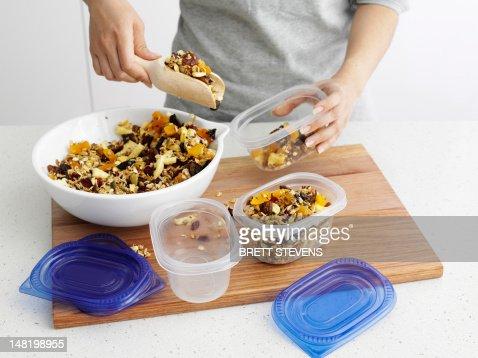 Woman scooping granola into tupperware