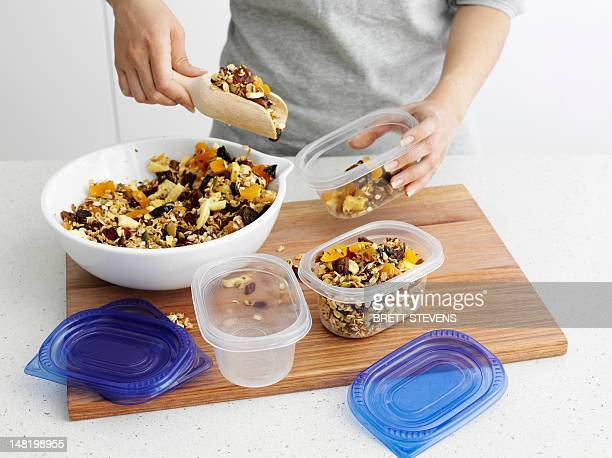 Woman scooping granola into tupperware