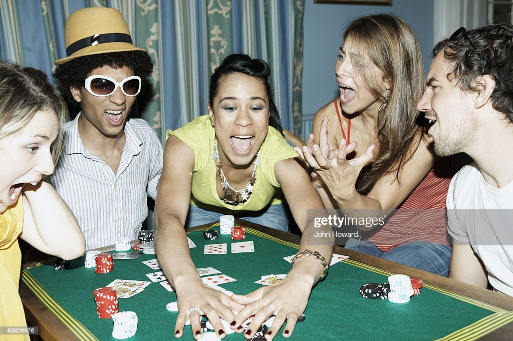 Woman scooping up her winnings from card game : Stock Photo
