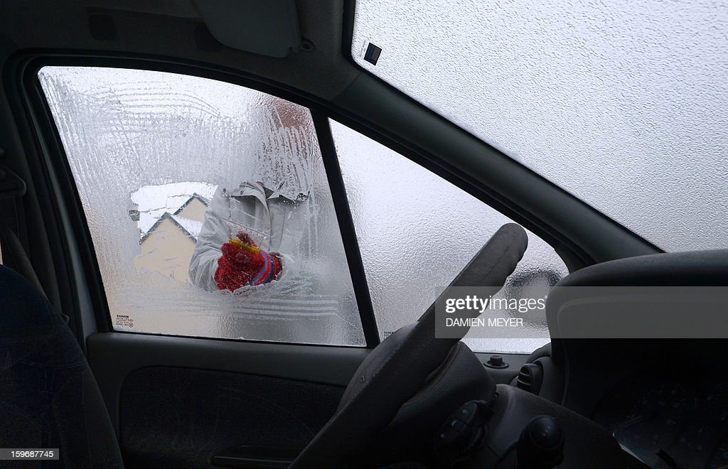 A woman scrapes ice off her car window as temperatures plummeted across France on January 18, 2013 next to the westen city of Rennes.