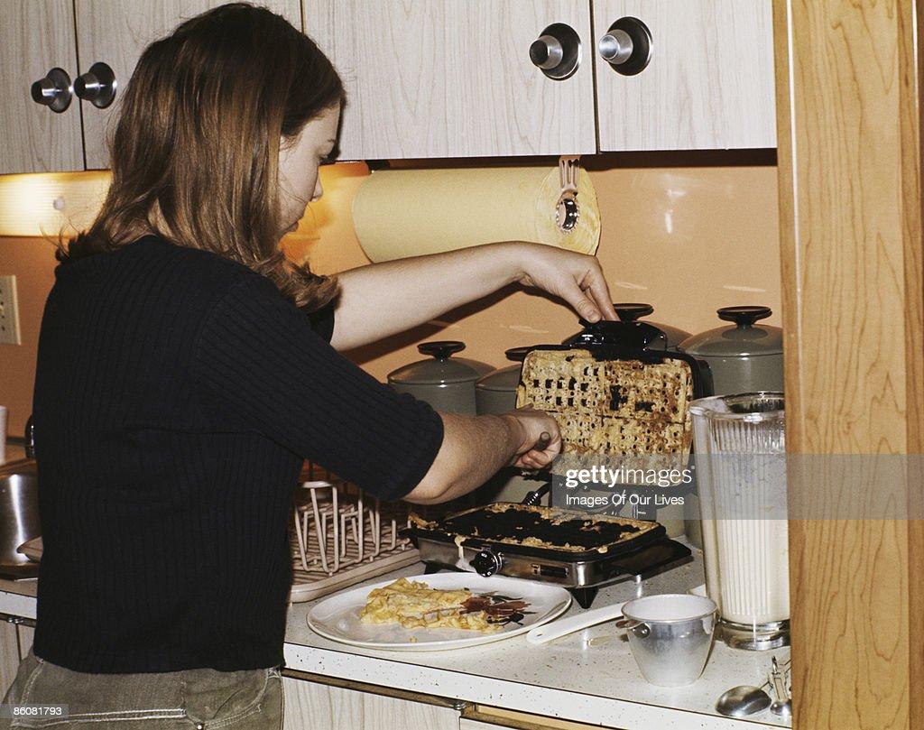 Woman scraping batter off waffle iron