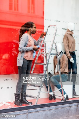 Woman scraping tape from shop window : Stock Photo