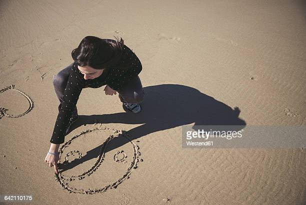 Woman scratching Yin Yang symbol in the sand of a beach
